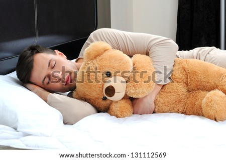 portrait of a young man sleeping on the bed embracing his soft toy - stock photo