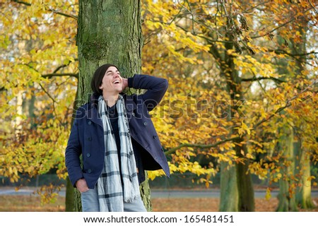 Portrait of a young man smiling outdoors in the countryside on a autumn day - stock photo