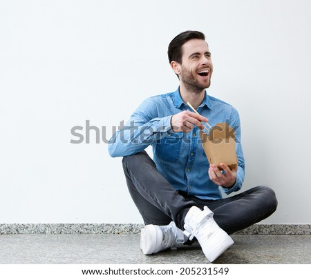 Portrait of a young man smiling with asian food and chopsticks - stock photo