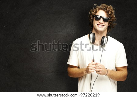 portrait of a young man smiling with headphones against a grunge wall - stock photo