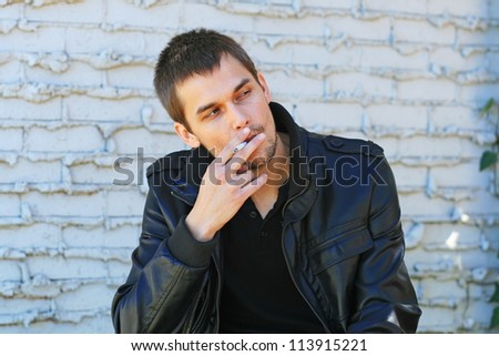 Portrait of a young man smoking in a park - stock photo