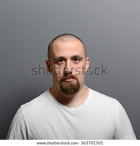 Portrait of a young man standing against gray background - stock photo