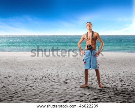 Portrait of a young man standing on a beach with a camera hanging from his neck - stock photo