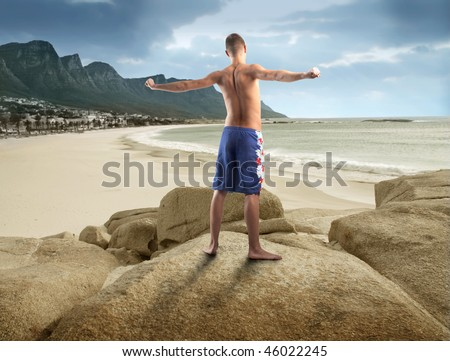 Portrait of a young man standing on a rock looking over the seaside and doing some gym - stock photo