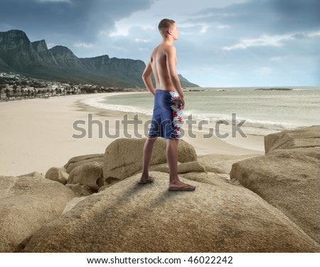 Portrait of a young man standing on a rock looking over the seaside and observing the panorama in front of him - stock photo