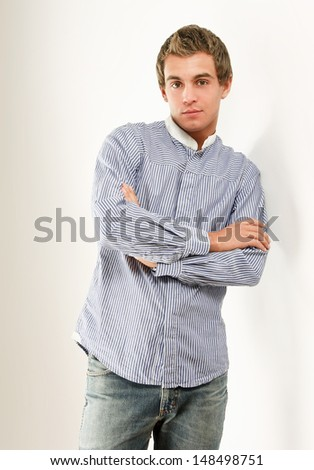 Portrait of a young man standing with folded arms, isolated on white background - stock photo