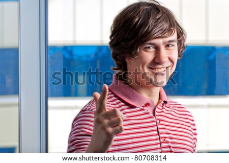 Portrait of a young man standing with his hands in pocket - stock photo
