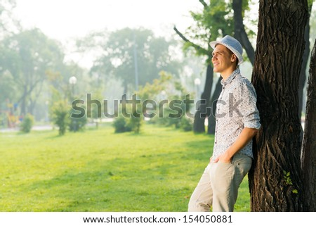 portrait of a young man, stands leaning against a tree in a summer park