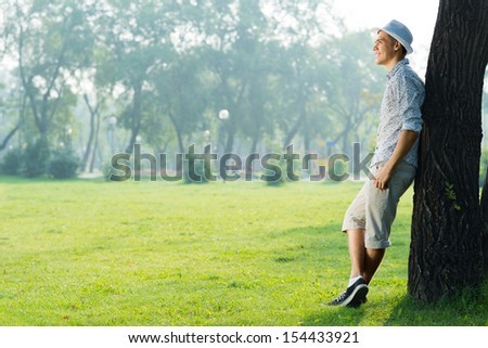 portrait of a young man, stands leaning against a tree in a summer park - stock photo