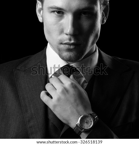 Portrait of a young man straightens his tie. Studio photo. - stock photo