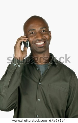 Portrait of a young man talking on a mobile phone smiling - stock photo