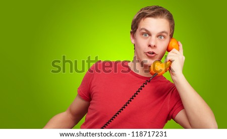 Portrait of a young man talking on vintage phone on green background - stock photo