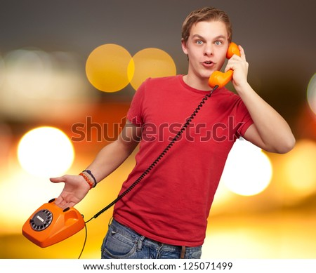 Portrait of a young man talking on vintage phone, outdoor - stock photo
