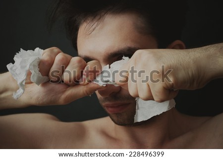 Portrait of a young man tearing paper - stock photo