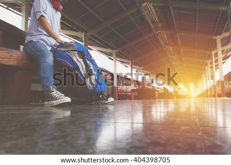 Portrait of a young man traveler waiting for train and travel bag. - stock photo