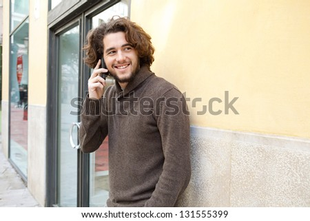 Portrait of a young man using a cell phone to make a call while standing by an office building entrance, outdoors. - stock photo