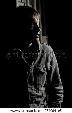 Portrait of a young man waiting in shadow - stock photo