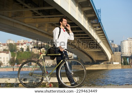 Portrait of a young man walking with bicycle and talking on mobile phone - stock photo