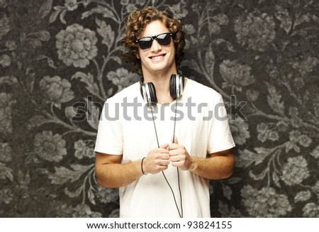 portrait of a young man wearing headphones against a vintage wall