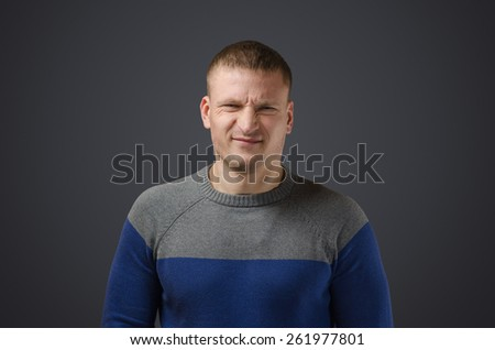 Portrait of a young man who is dissatisfied with something. Emotional photo in studio on a black background. - stock photo