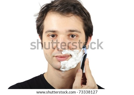 portrait of a young man who is shaving himself - stock photo