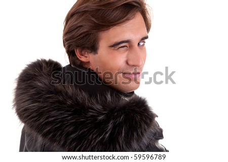 Portrait of a young man winking from back, in autumn/winter clothes, isolated on white. Studio shot
