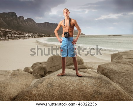Portrait of a young man with a camera standing in on a rock looking over a beach - stock photo