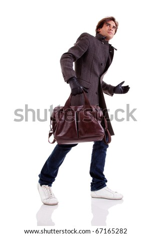 Portrait of a young man with a handbag, hasty, in autumn/winter clothes, isolated on white. Studio shot - stock photo