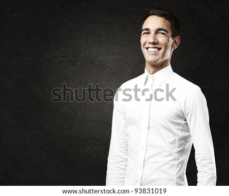 portrait of a young man with a shirt smiling against a grunge wall - stock photo