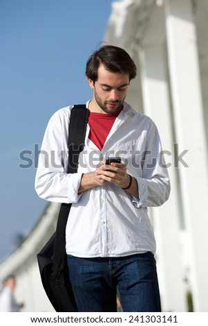 Portrait of a young man with bag walking and sending text message outdoors - stock photo