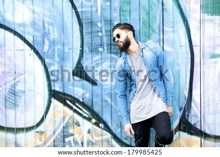 Portrait of a young man with beard and sunglasses relaxing against graffiti background outdoors - stock photo
