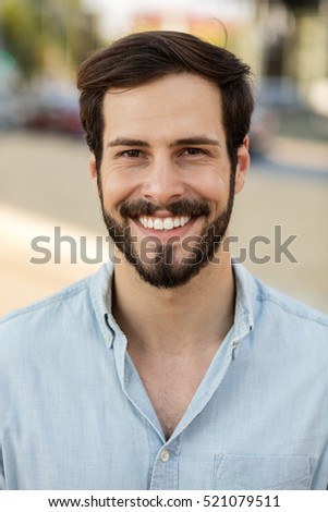 portrait of a young man with beard looking masculine outside on the street