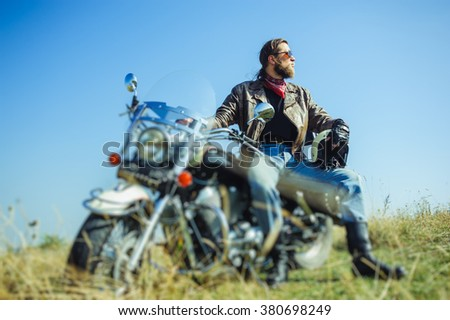 Portrait of a young man with beard sitting on his cruiser motorcycle and looking to the sun. Man is wearing leather jacket and blue jeans. Low point of view. Tilt shift lens blur effect - stock photo