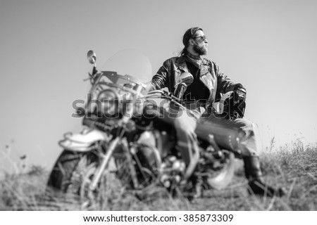 Portrait of a young man with beard sitting on his cruiser motorcycle and looking to the sun. Man is wearing leather jacket and blue jeans. Low point of view. Tilt lens blur effect. Black and white - stock photo
