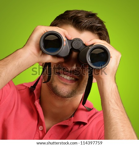 Portrait Of A Young Man With Binoculars Over A Green Background - stock photo