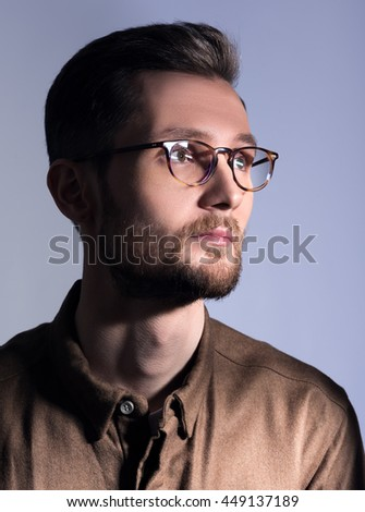 Portrait of a young man with glasses and a beard. Neutral facial expression. Grey background - stock photo