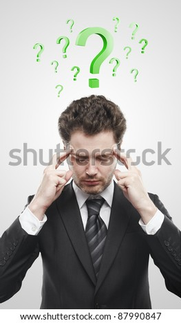 Portrait of a young man with green question marks above his head.Conceptual image of a open minded man. On a gray background - stock photo