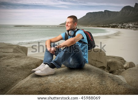 Portrait of a young man with headphones and a rucksack sitting on a rock looking over a coastline - stock photo