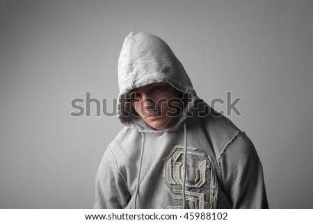 Portrait of a young man with his face covered by the hood of his sweatshirt - stock photo