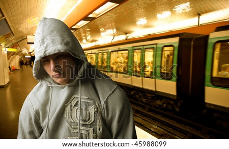 Portrait of a young man with his face covered by the hood of his sweatshirt standing on the platform of an underground station - stock photo