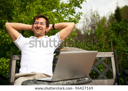 Portrait of a young man with laptop outdoor sitting on bench - stock photo