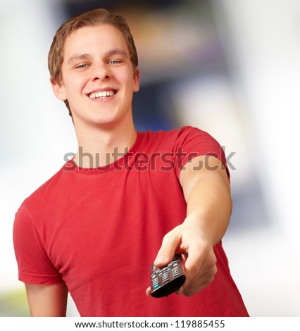 portrait of a young man with remote control, background - stock photo