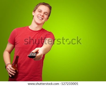 portrait of a young man with remote control on green background - stock photo