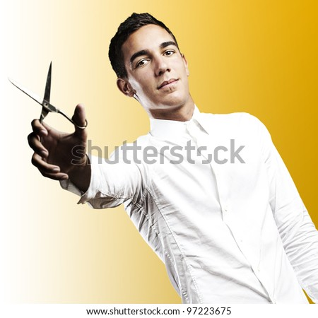 portrait of a young man with scissors on a yellow background - stock photo