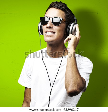 portrait of a young man with sunglasses listening to music on a green background - stock photo