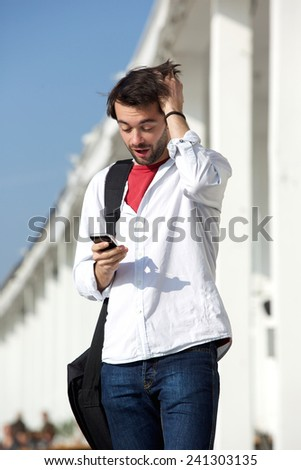 Portrait of a young man with surprised expression looking at mobile phone text message - stock photo