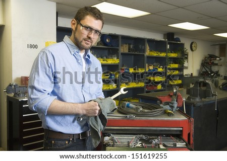 Portrait of a young man with tools working in workshop