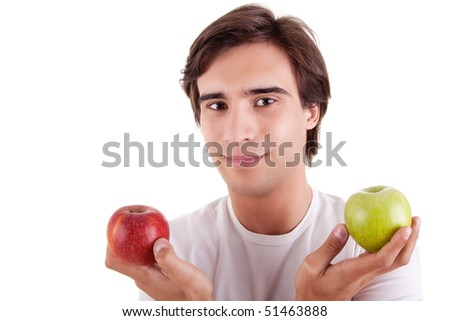 Portrait of a young man with two apples in their hands: green and red. Concept of choice, on white background. Studio shot - stock photo