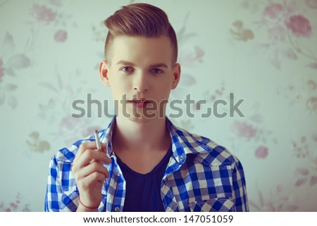 Portrait of a young man with very handsome face in blue casual shirt & t-shirt with stylish haircut holding a cigarette and smoking over vintage background. Hipster style. Close up. Copy-space - stock photo