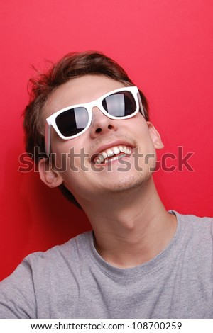 portrait of a young man with white sunglasses on red - copy space - stock photo